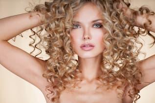 Blonde Frau mit perfekt sitzender Dauerwelle greift sich mit beiden Händen in das voluminöse Haar