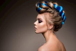 Junge Frau mit Hochsteckfrisur und Zopf mit extrem hellblauer Strähne im Zopf - sie wirkt jung, modisch und modern für ein Event gestylt.