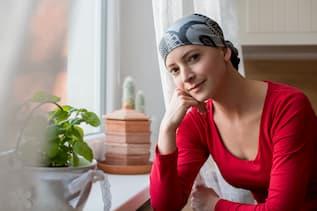 Frau sitzt mit Bandana auf dem Kopf und sieht beim Fenster hinaus.