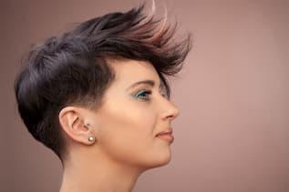 Kopf einer Frau mit einem trendigen Fashion Cut. Die Frau ist seitlich zu sehen und dezent geschminkt. Sie hat azurblaue Lider und gepflegte Augenbrauen. Ihr Haar ist vorne leicht aufgestellt und hat dezente graue und rötliche Mechen.