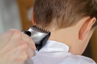 Hinterkopf eines Kindes, Meisterfriseur Artner schneidet Konturenschnitt mit Maschine
